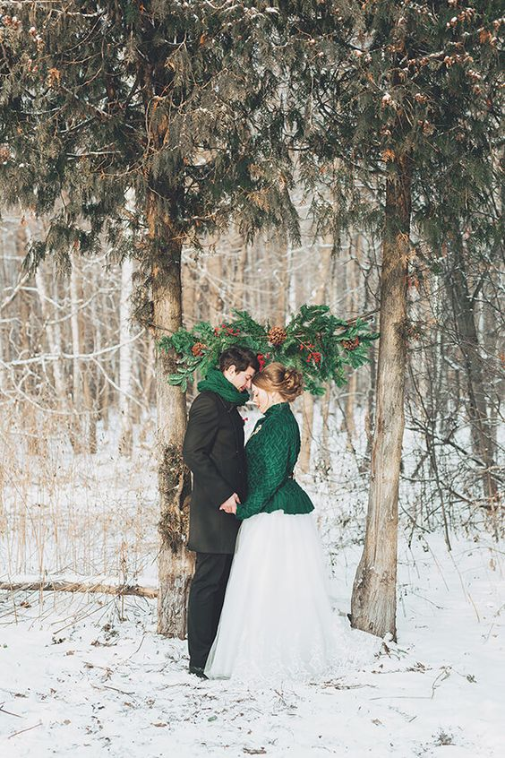 a creative wedding arch formed of two living trees and some evergreen branches attached to them plus pinecones and berries