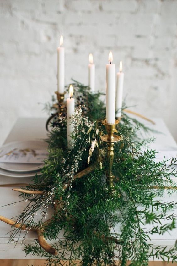 a simple winter wedding centerpiece of evergreens, little blooms and candles in candle holders for a Nordic wedding