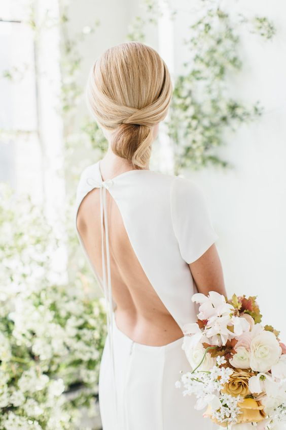 a sleek minimalist twisted low updo with a sleek top is ideal for a minimalist bride