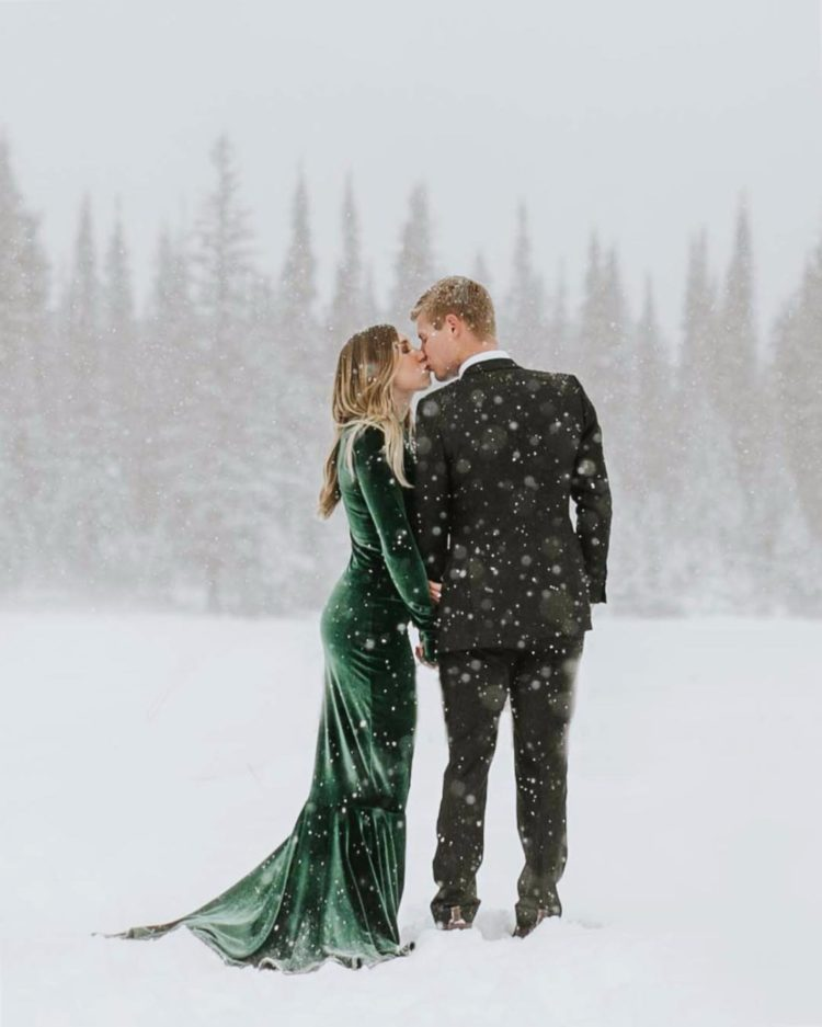 an emerald velvet fitting wedding dress with long sleeves and a train for a colorful touch at your Christmas wedding