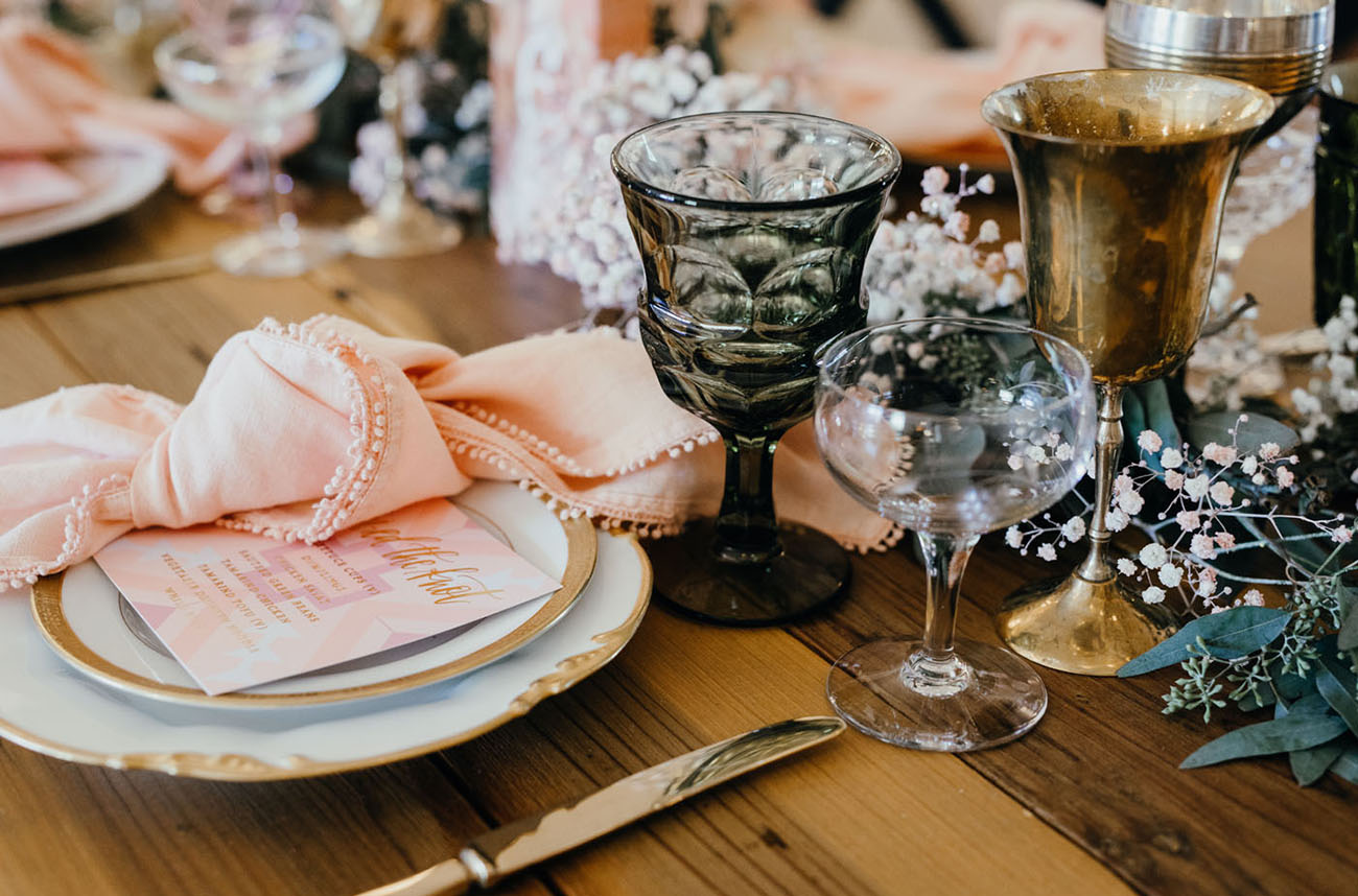 The gold golblets, colored glasses, baby's breath and pink pompom napkins added to the table settings