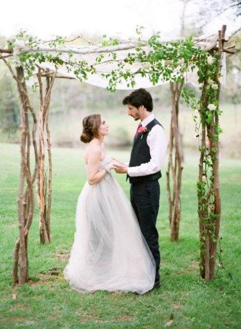 a cute natural wedding arbor made of branches and decorated with airy white fabric and greenery plus blooms for a spring wedding