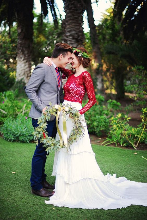 a strapless white wedding gown with a ruffled skirt with a train and a red lace top with long sleeves over it