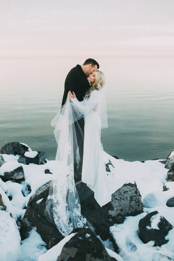 a wedding portrait of the couple on a frozen and snowy lakeshore looks like a real winter fairy-tale