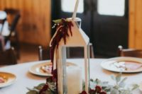 11 a winter wedding centerpiece of a white lantern with maroon blooms and greenery