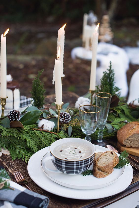 a winter wedding centerpiece of evergreens, ferns, snowy pinecones, cotton and candles in candle holders for a Christmassy table setting
