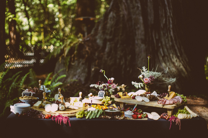 The couple styled a cool cheese and fruit table decorated with moody florals