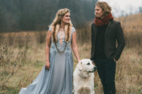 a blue wedding gown with a lace illusion bodice cap sleeves and a pleated skirt with a train and a faux fur scarf on top