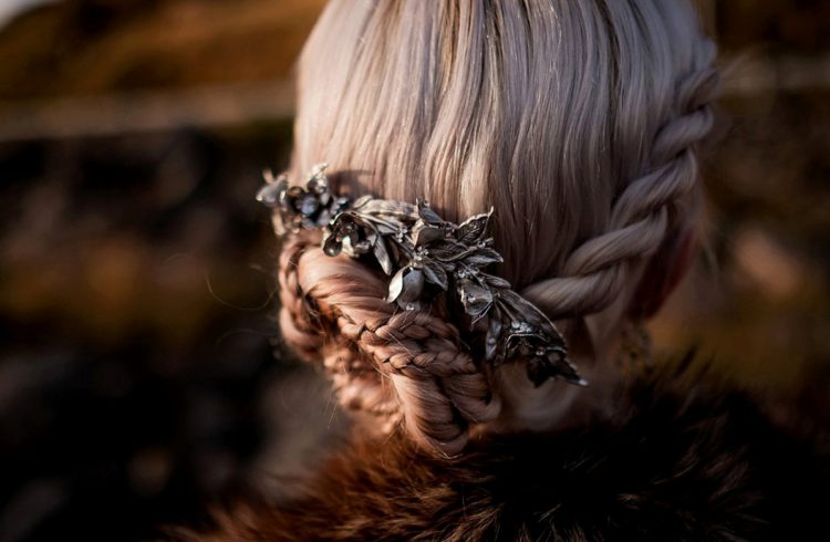 a braided and twisted low bun integrating several braids at once and accessorized with a vintage hairpiece with rhinestones