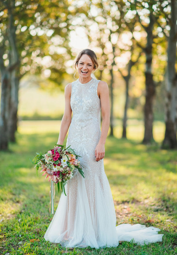 a fully embellished sleeveless wedding gown with a high neckline and a semi-sheer skirt for a glam bride