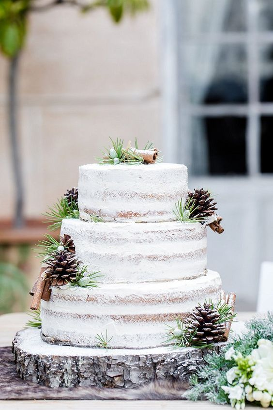 a naked wedding cake with piecones, cinnamon bark and greeneery to follow the trend of naked cakes