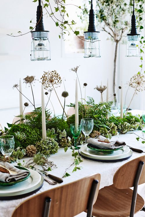 a woodland style wedding centerpiece of greenery, succulents, dired blooms and pinecones for a Nordic woodland summer or fall wedding