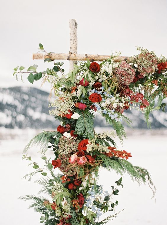 an outdoor rustic wedding arch with evergreens, white and red flowers will stand out in a snowy location