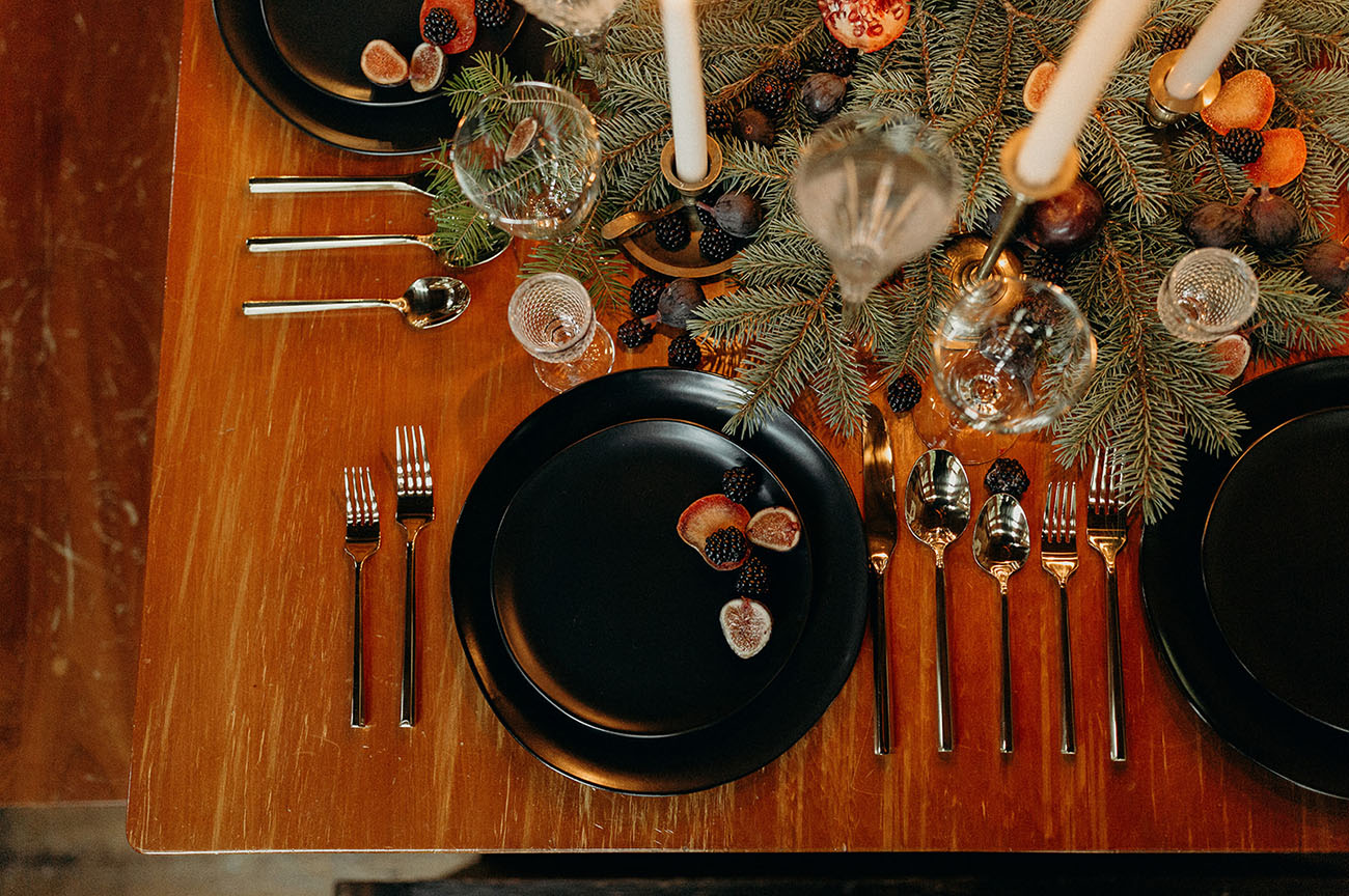 The table setting was done with evergreens, blackberries, blueberries, pomegranates and candles plus modern black chargers and plates