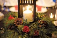13 a Christmas centerpiece of a wreath of evergreens, pinecones and red roses and a lantern with a candle