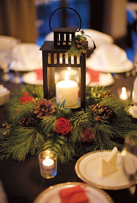 a Christmas centerpiece of a wreath of evergreens, pinecones and red roses and a lantern with a candle