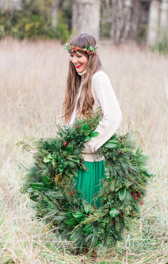 a large and lush evergreen wedding wreath with berries and foliage is a cool decoration for a winter Scandinavian wedding