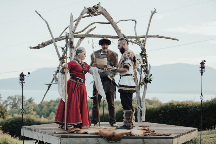 a viking-inspired wedding ceremony arch of driftwood on a platform with a fake animal skin and runs hanging on the arch