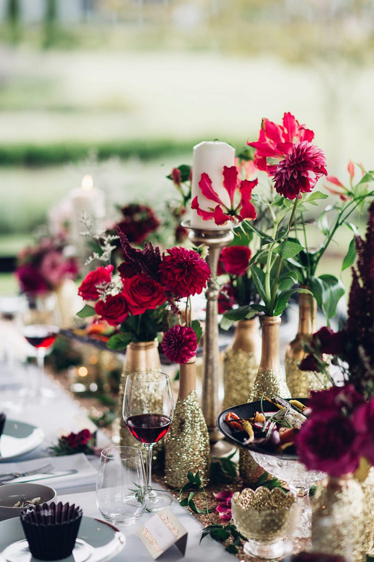 small vases made of gold and gold glitter bottles with bright red blooms and greenery for a festive tablescape