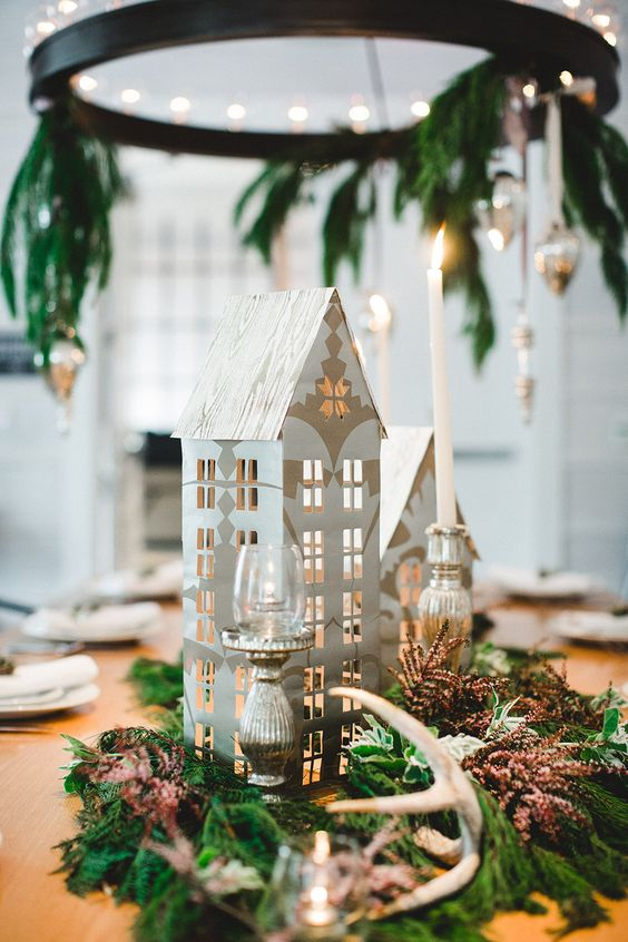 a Nordic winter wedding centerpiece of ferns, dried herbs, antlers, candles and cardboard houses are a cool non-floral option