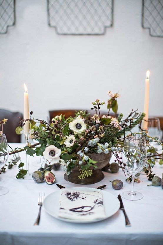 a beautiful and natural wedding centerpiece with textural greenery, evergreens, anemones and berries plus candles for a Scandinavian winter wedding