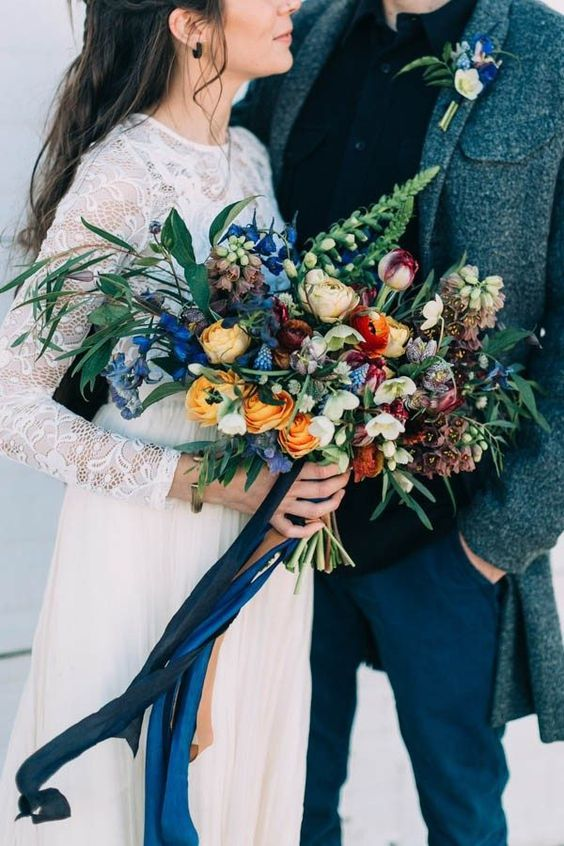 a colorful wedding bouquet with blue, orange, red and burgundy blooms and grasses of different kinds