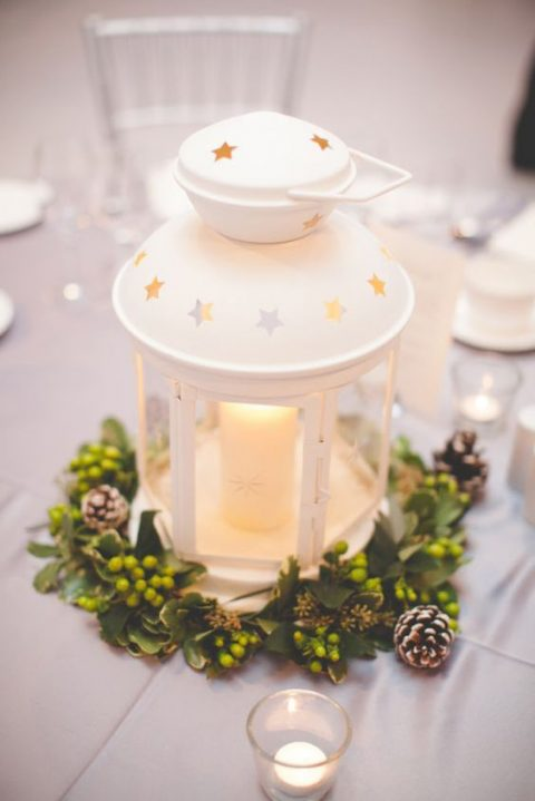 a white IKEA lantern centerpiece with a greenery wreath with berries and pinecones is ideal for Christmas