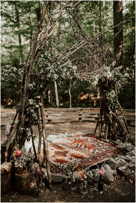 a wild wedding arch of branches, foliage, neutral blooms, rocks around and a boho carpet for a Nordic woodland ceremony