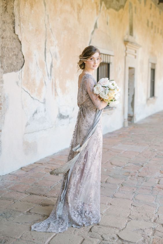 an airy grey lace wedding gown with long sleeves and a cutout back for an ethereal bridal look