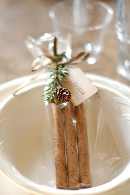 cinnamon bark topped with twigs and a pinecone is a  truly Christmas wedding favor