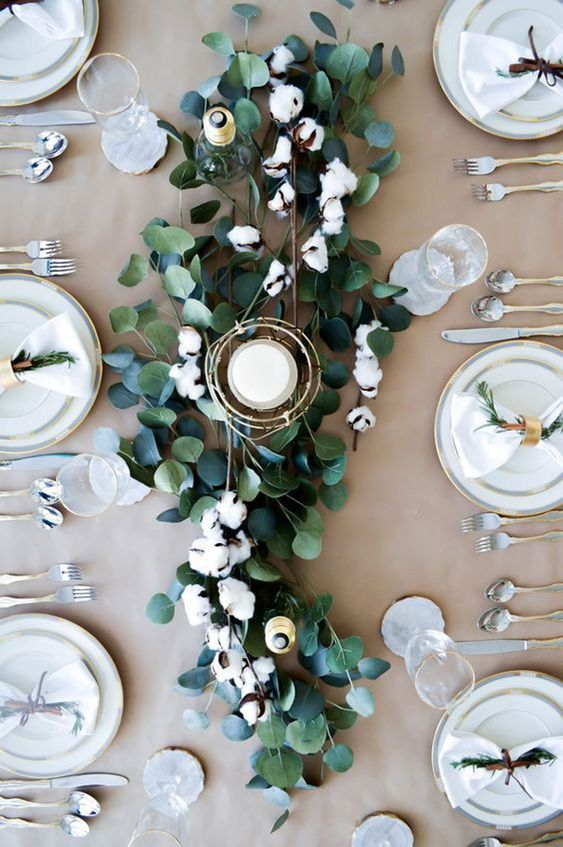 a chic and easy centerpiece of eucalyptus, cotton and a candle in a gilded candle holder for a winter Nordic wedding