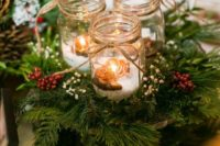 15 a cozy Christmas centerpiece of evergreens, berries, candle lanterns with fake snow