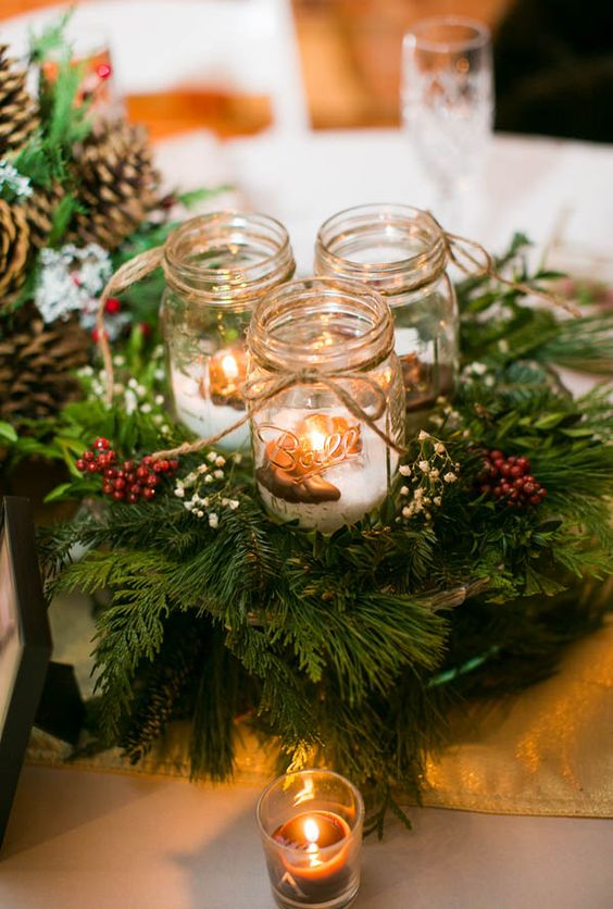 a cozy Christmas centerpiece of evergreens, berries, candle lanterns with fake snow