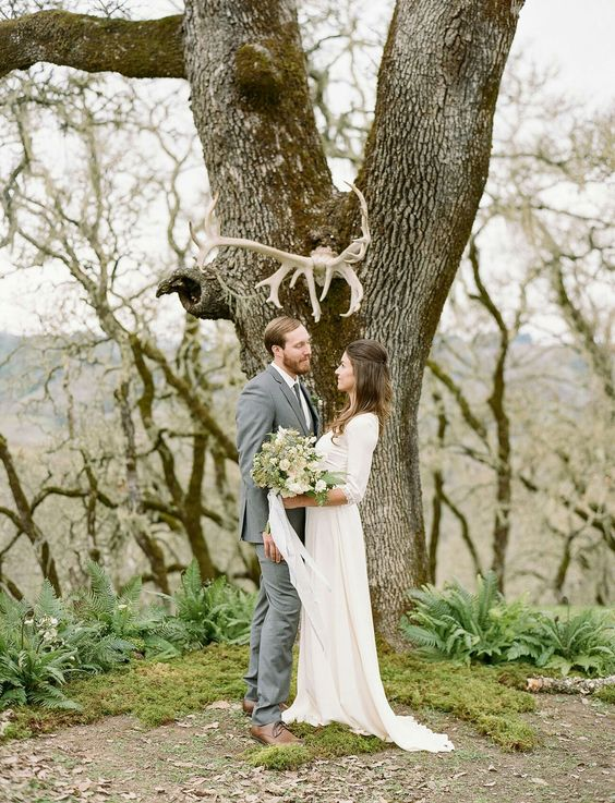 a living tree covered with moss and with antlers attached is great for a moody Scandinavian wedding, plus it's eco-friendly