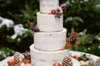15 a semi naked wedding cake topped with dark blooms, berries, apples and gilded pinecones