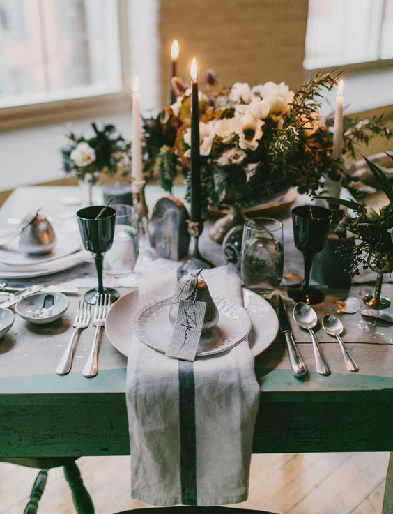 a winter wedding tablescape with neutral napkins, black glasses, white floral centerpiece and black and white candles plus silver cutlery