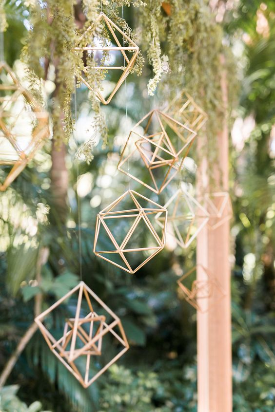 hanging gold himmeli pendants and cascading greenery on the wedding arch make the ceremony space more modern and trendy