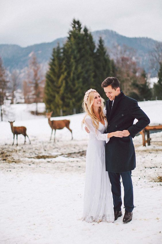 winter wedding portraits in a snowy location with real deer is a very cool and romantic idea