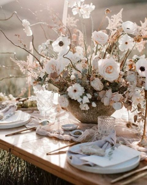 a delicate and dimensional wedding centerpiece of white and blush blooms and dired herbs in a cool bowl for a romantic Nordic spring wedding