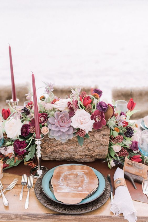 a luxurious boho chic wedding centerpiece in the shades of burgundy, plum, pink, red plus colorful succulents