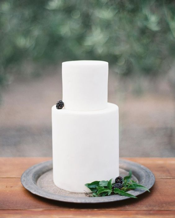 a pure white wedding cake topped with a single blackberry and displayed with greenery and blackberries for late summer