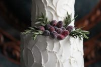 17 a white textural buttercream wedding cake with evergreens and sugared berries for a clean yet catchy look