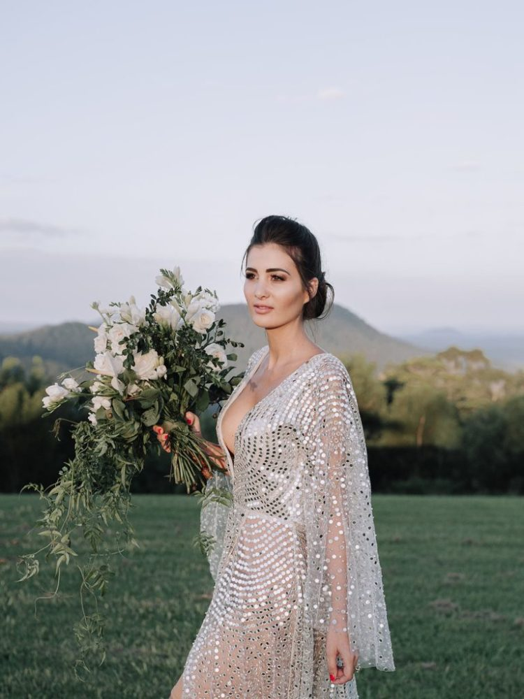a gorgeous modern wedding dress with a nude underdress, wide sleeves and a plunging neckline and large sequins