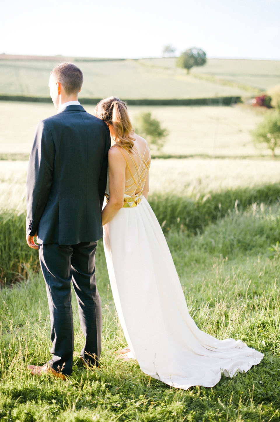 a modern A line wedding dress with an embellished geometric sash and multiple criss cross gold and white straps