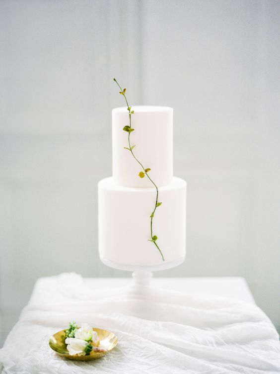 a pure white minimalist wedding cake decorated with a single fresh twig is amazing for a spring wedding