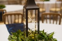 18 a simple and cozy Christmas wedding centerpiece with fresh greenery and a lantern filled with LEDs