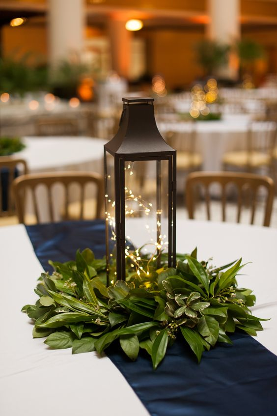 a simple and cozy Christmas wedding centerpiece with fresh greenery and a lantern filled with LEDs