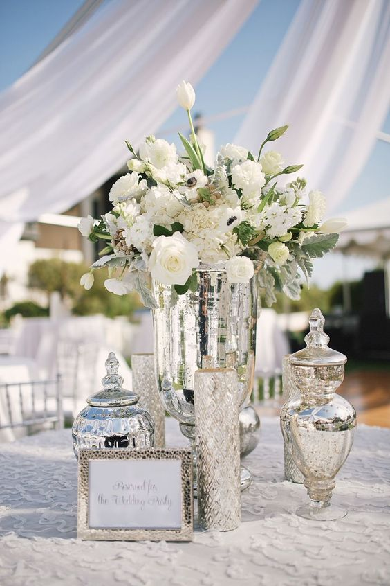 mercury glass vases and jars plus white blooms compose a classic and chic wedding centerpiece
