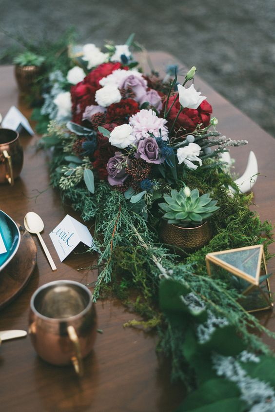 a lush Nordic wedding centerpiece of bold blooms, evergreens, succulents, antlers and geometric candle lanterns