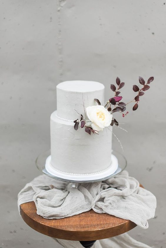 a purely white wedding cake decorated with dark foliage and a single white blooms for an early fall wedding with a Nordic twist